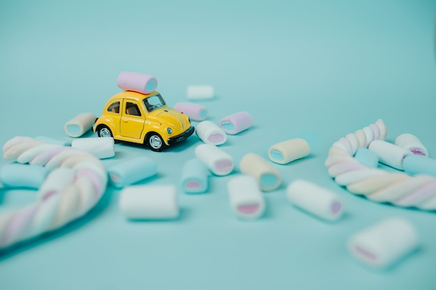 Guimauve colorée. beaucoup de bonbons sur la table. voiture jouet jaune avec guimauve torsadée et bonbons autour.