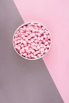Guimauve colorée disposée sur la surface du papier rose et gris