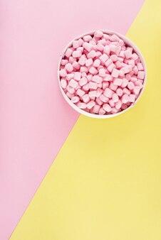 Guimauve colorée disposée sur la surface du papier rose et jaune