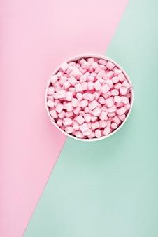 Guimauve colorée disposée sur la surface du papier rose et menthe