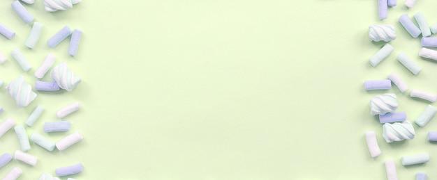 Guimauve colorée posée sur du papier citron vert. cadre texturé créatif pastel