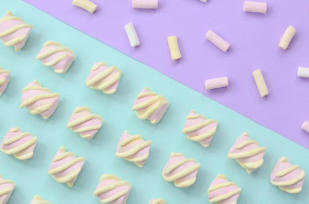Guimauve colorée posée sur du papier violet et bleu