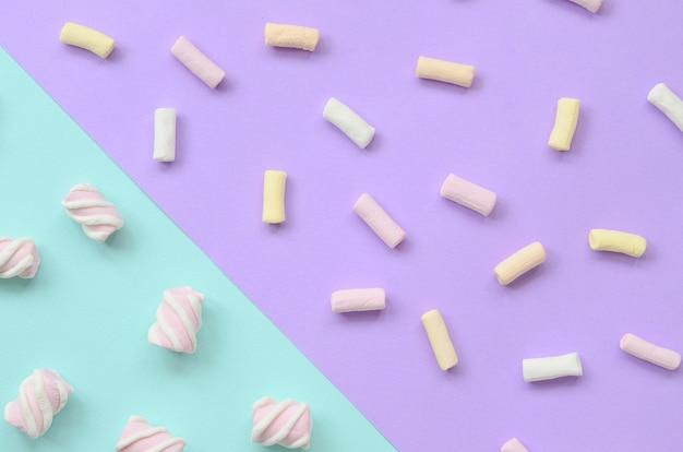 Guimauve colorée posée sur fond de papier violet et bleu