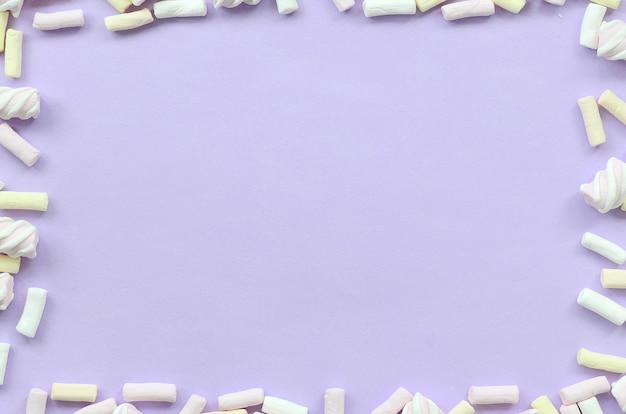 Guimauve colorée posée sur fond de papier violet