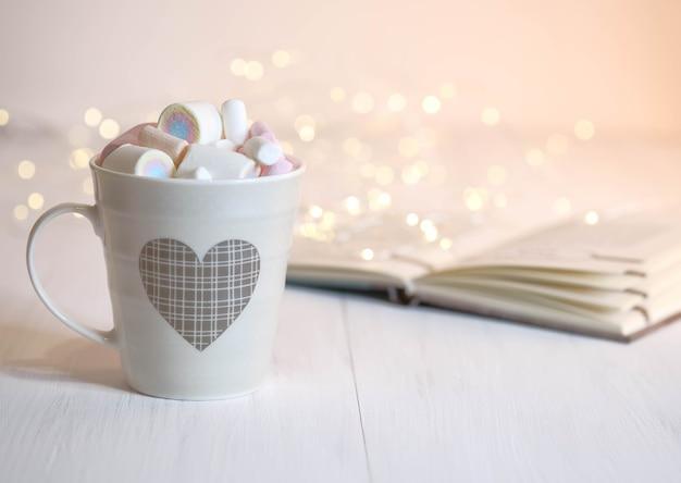 Guimauve et dans une tasse avec un motif et un livre sur la table