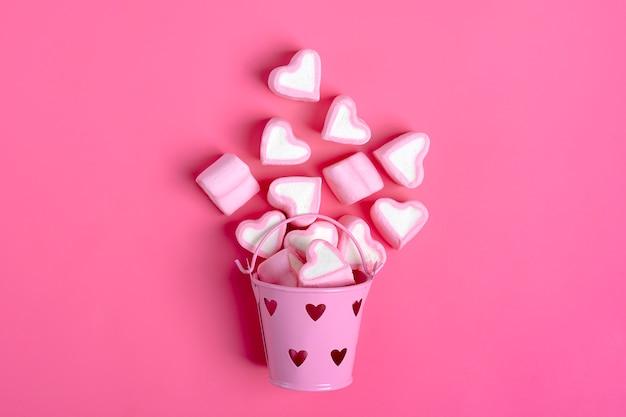 Guimauve en forme de coeur renversé de seau sur fond rose bonne saint valentin