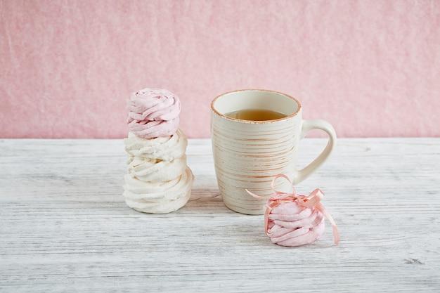 Guimauve rose et blanche douce maison - zéphyr sur une table en bois clair.