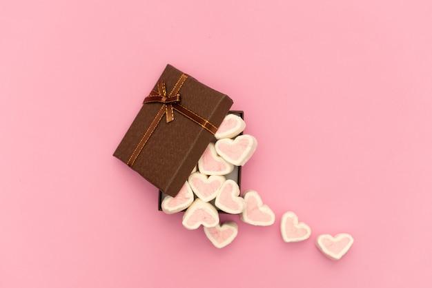 Guimauve rose dans une boîte cadeau en forme de coeur sur fond textile, beaucoup de coeurs guimauves pour le présent, bonbons en forme de coeurs de guimauves. cadeau saint valentin