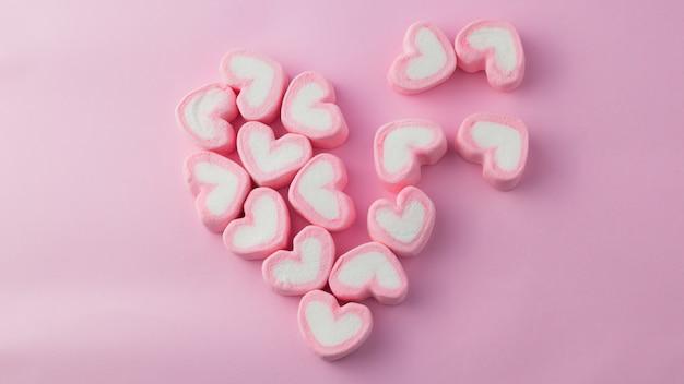 Guimauve rose en forme de coeur avec fond rose