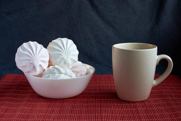 Guimauve zéphyr blanc et rose avec capuchon de tee sur assiette en porcelaine