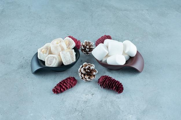 Guimauves blanches douces avec des pommes de pin sur marbre.