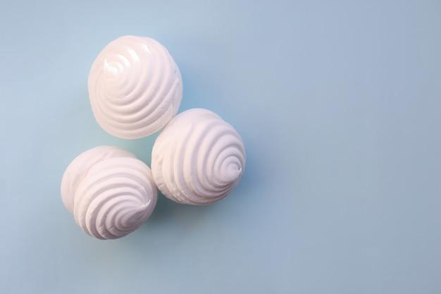 Guimauves blanches sur fond bleu. lay à plat, espace de copie