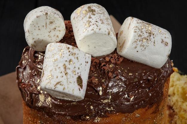 Guimauves blanches saupoudrées d'or sur glaçage au chocolat sur gâteau de pâques