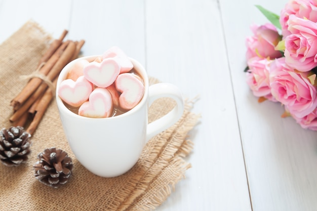 Guimauves coeur rose sur chocolat chaud dans une tasse blanche. concept d'amour