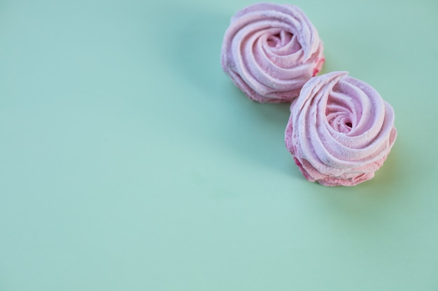 Guimauves maison roses ou zephyr. désert sucré et sucré sur un mur vert pastel. biscuits au sucre copiez l'espace. ensemble de berry souffle, meringue maison.