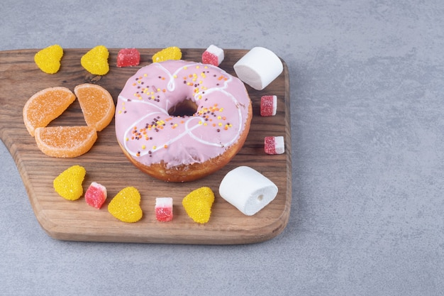 Guimauves, marmelades et un beignet sur une planche de bois sur une surface en marbre