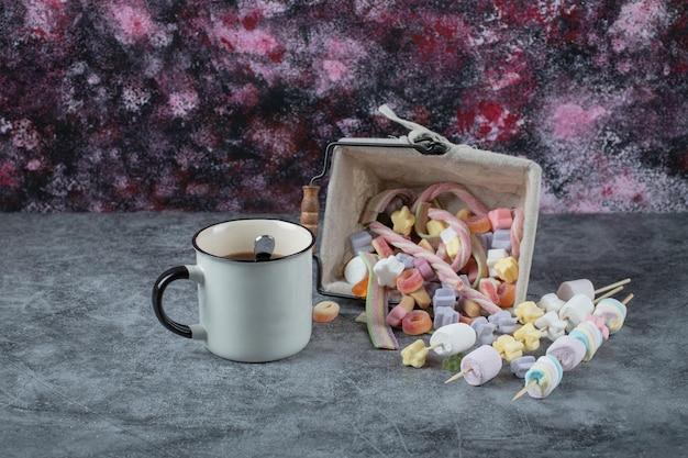 Guimauves multicolores sur panier avec une tasse de thé de côté.