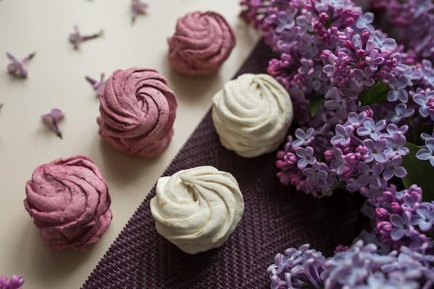 Guimauves roses et blancs sur une table avec des fleurs lilas. bonbons et nourriture dans la cuisine.