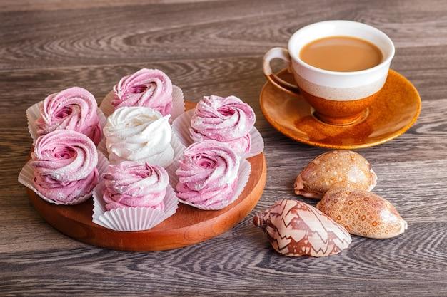 Guimauves roses et blancs (zephyr) sur une planche de bois ronde avec une tasse de café
