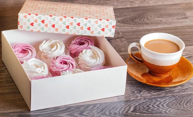 Guimauves roses et blancs (zephyr) avec une tasse de café sur un fond en bois gris