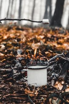 Les guimauves rôtissent sur le feu de camp et deviennent bien dorées.