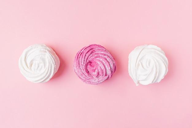 Guimauves vanille et baies fraîches sur fond rose pastel.