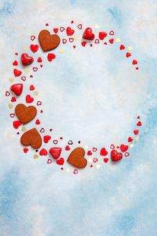 Guirlande de bonbons, biscuits et figurines de coeur sur fond bleu.