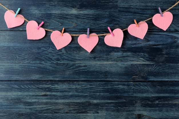 Une guirlande de coeurs sur des pinces à linge sur un fond en bois bleu la saint-valentin.