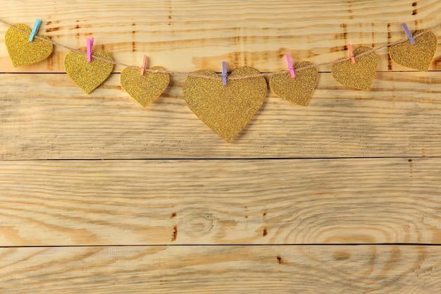 Une guirlande de coeurs sur des pinces à linge sur un fond en bois naturel saint-valentin.