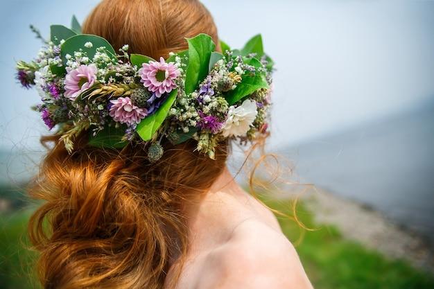 Guirlande de différentes fleurs sauvages sur la tête pour la mariée