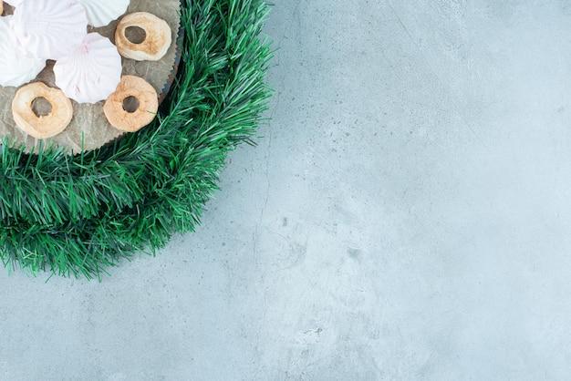 Guirlande enroulée autour d'une planche avec des biscuits et des tranches de pommes sèches sur du marbre.
