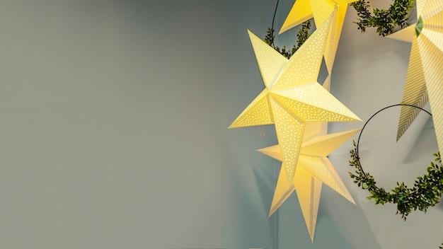 Guirlande festive en forme d'étoile dorée avec des couronnes pour noël, nouvel an sur fond gris.