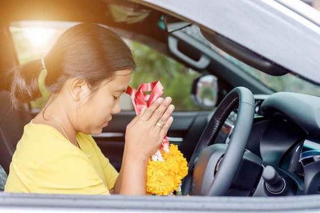 Guirlande de fleurs femme à la main et priant dans la nouvelle voiture pour la chance