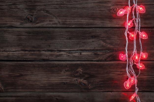 Guirlande en forme de coeur rouge sur vieux bois foncé