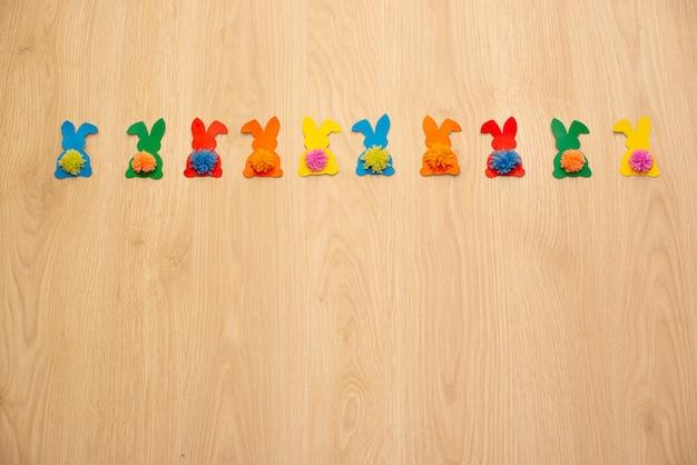 Guirlande de lapins colorés sur table en bois.