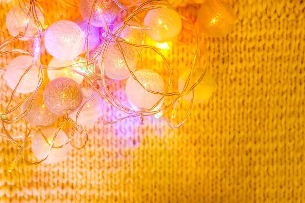 Guirlande de lumières de noël avec des lanternes rondes sur fond de tissu tricoté.