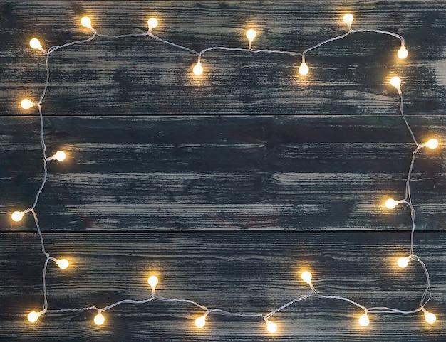 Guirlande de lumières de noël rondes avec des couleurs chaudes placées sous la forme d'un cadre sur fond sombre de planches de bois