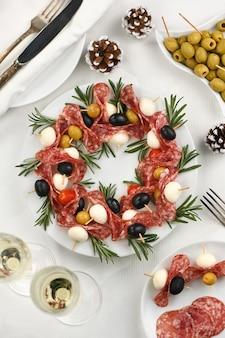 Guirlande de noël d'antipasto. canapés de salami aux olives et mozzarella.