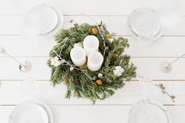 Guirlande de noël avec des bougies blanches sur la table de fête avec des assiettes