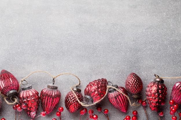 Guirlande de noël avec boule rouge et fond gris.