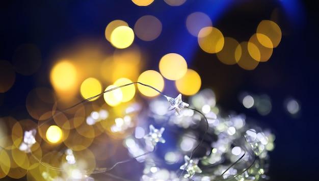 Guirlande de noël de bouteilles en verre, bocaux avec une plante à l'intérieur. concept de nouvel an et de noël. une guirlande d'ampoules avec une belle lumière et un bokeh