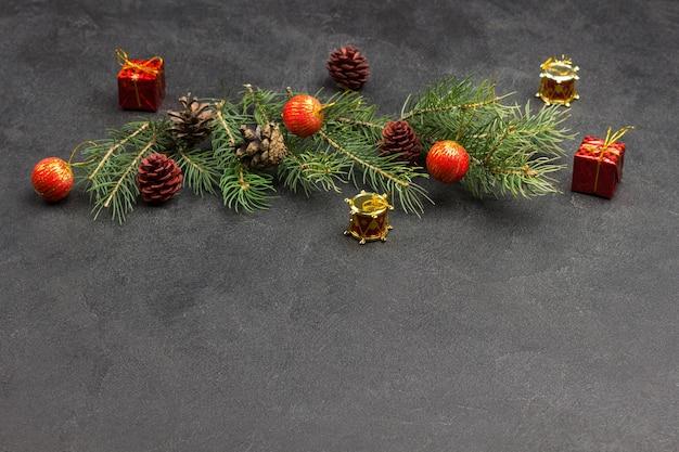 Guirlande de noël. branches de sapin, cônes, jouets rouges. vue de dessus. copiez l'espace. fond noir
