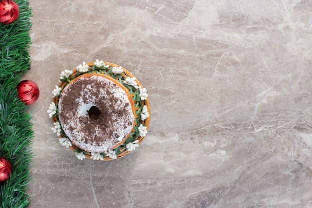Guirlande de noël à côté d'un seul beignet sur marbre.