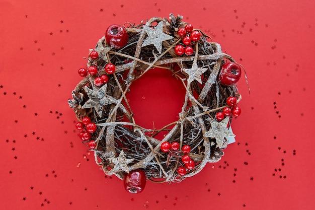 Guirlande de noël faite de branches décorées d'étoiles en bois d'or et de bulles de fruits rouges isolés sur fond rouge