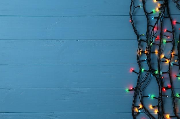 Guirlande de noël s'allume sur fond bleu, espace copie