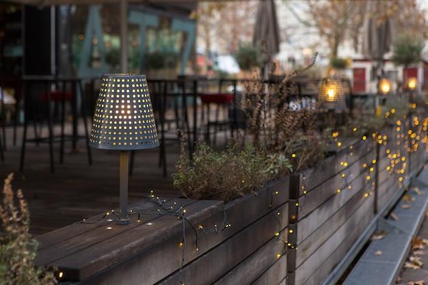 Guirlande de noël sur la terrasse. une lampe du soir illumine l'intérieur en bois.