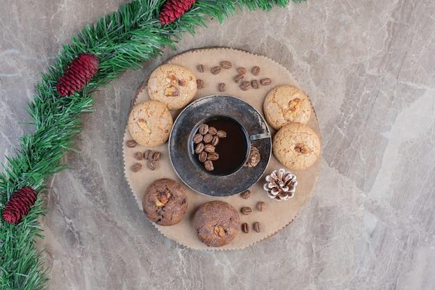 Guirlande ornée de pommes de pin à côté d'un plateau de biscuits et de café sur marbre.
