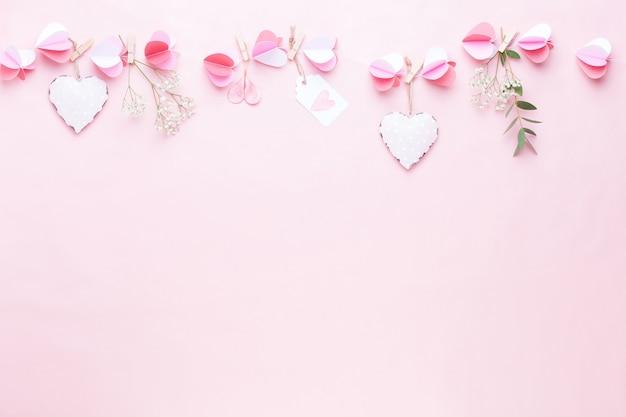 Guirlande en papier coloré de coeurs sur le fond de corail vivant. cartes de voeux saint valentin.