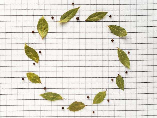 Guirlande posée sur une nappe de feuilles de laurier et de poivre noir. espace pour le texte