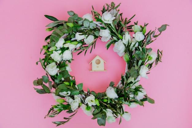 Guirlande de roses blanches et nichoir sur fond rose. décoré. vue ci-dessus